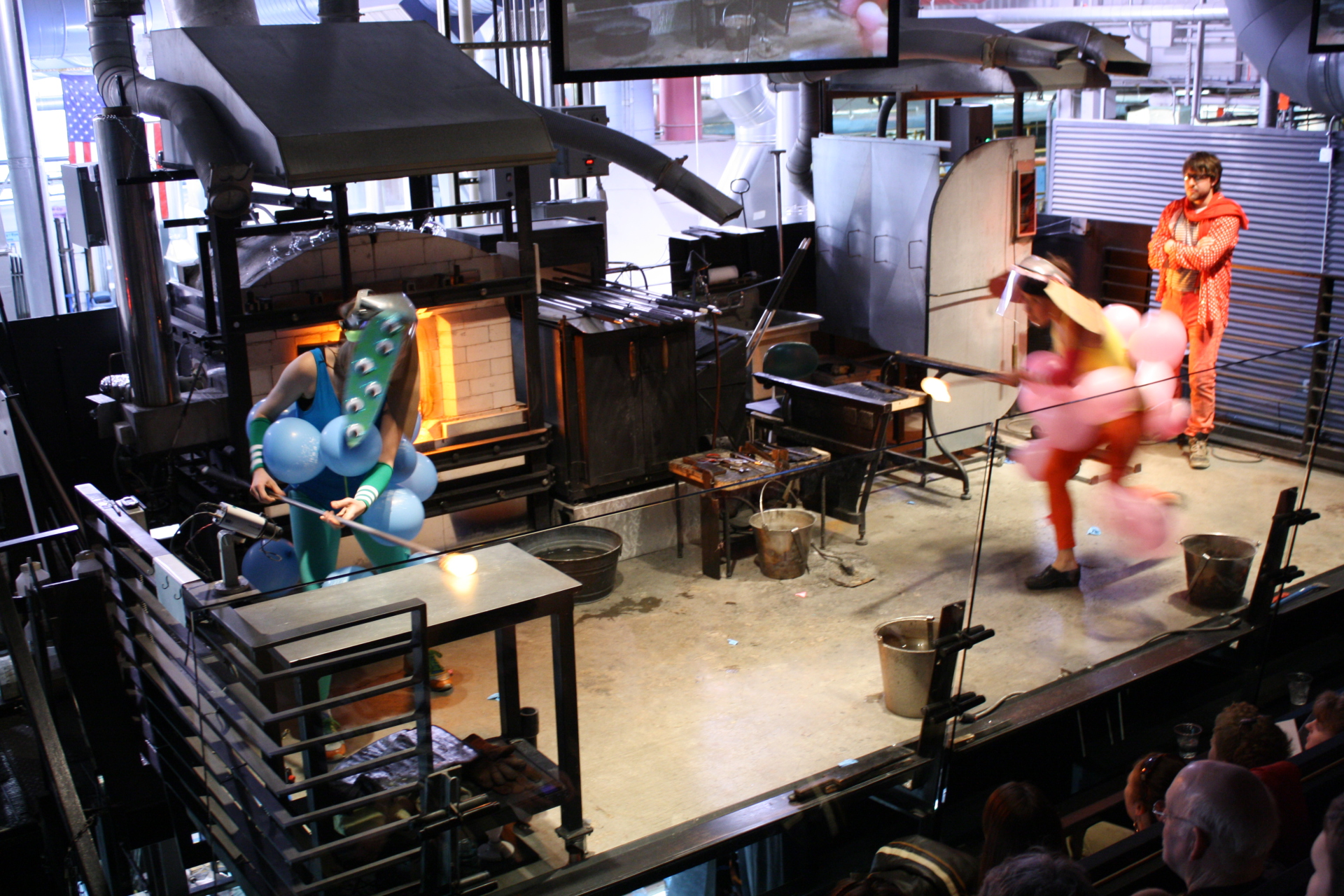 A glassblower in an unusual pink costume runs across the hotshop stage with molten glass on the end of a blowpipe, towards another glassblower in a blue costume.