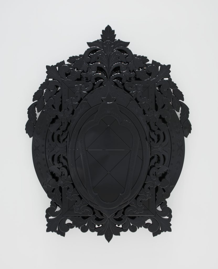 Looking into an ornate, oval-shaped mirror that has a black backing making any object reflected in it's surface appear black.