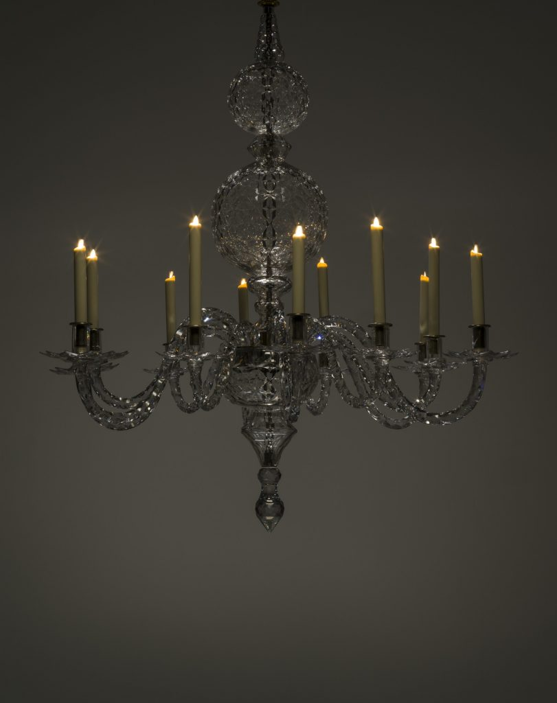 a crystal chandelier with 12 arms each holding a candle that is lit.