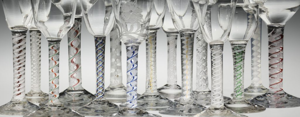 Image of the stems of 15 wine glasses stood in a row left to right. Each stem has an intricate twist pattern of various colors inside.